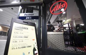 Till vänster syns en skylt där öppettider står listade, till vänster en skylt med texten alko. I bakgrunden syns en person med en kundvagn.