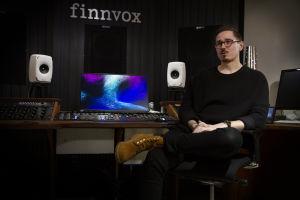 Mies istuu musiikkistudiossa, seinässä on Finnvoxin logo.