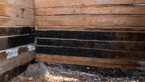 Stockvägg där de nedersta stockarna är svartbrända.