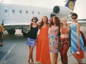 Viisi diivamaisesti pukeutunutta neitoa Lufthansan matkustajalentokoneen edessä.