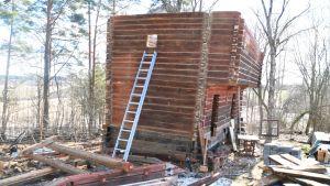 En röd stockbyggnad står på en gård med högar av material och bråte. Byggnaden saknar tak.