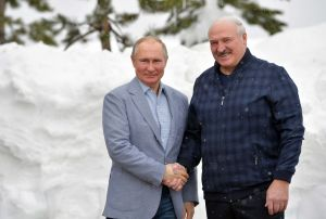 Rysslands president Vladimir Putin och Belarus president Aleksandr Lukasjenko skakar hand och tittar båda mot kameran.