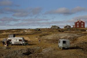 På bilden syns en skruttig husbil, några röda och bruna hus och en grå paketbil i ett fjällandskap.