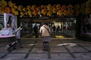 Toimittaja Jaana Semeri seisoo Stockmannin tavaratalon edessä Helsingin keskustassa ja katselee keltaisia kukkia