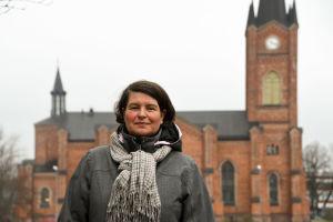 En kvinna står framför Lovisa kyrka.