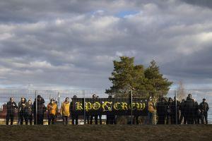 KuPS-anhängare bakom ett stängsel.