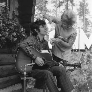 Naamioitsija Kristina Partio meikkaa folklaulaja Donovania Ohimennen-ohjelmaan Paimion motellin savusaunalla.