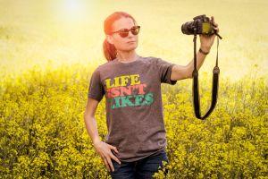 Nainen ottaa itsestään selfietä perinteisellä järjestelmäkameralla, ollaan valoisalla pellolla.
