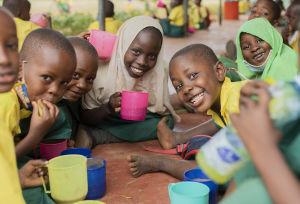 Makongenin kylän esikoululaiset juovat puuroa kupeista iloisin ilmein.