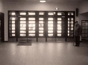 Eläkeikäinen mies seisoo kävelykepin kanssa rautatieaseman aulassa. Taustalla lasisia pariovia.
