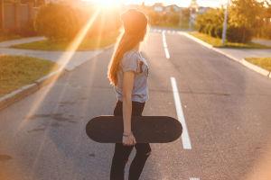 Tyttö kantaa skeittia kadulla, aurinko laskee.