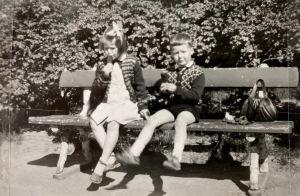 Kaksi lasta helsinkiläisellä puistonpenkillä taustalla pensasaita.