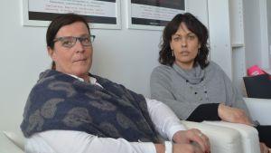 Bodil och Susann sitetr i soffa och tittar in i kameran med ganska allvarlig min.