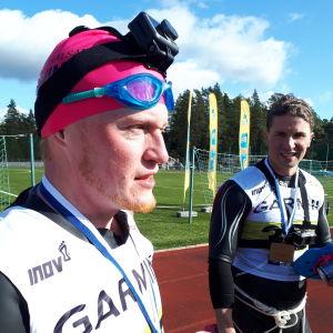 Två män i våtdräkt med medaljer runt halsen, den ena har dessutom en neonrosa simmössa. De är på ett sportplan. Blå himmel och sol. September 2020.