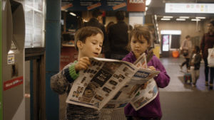 Kuusivuotiaat Aatos ja Flo lukevat Metro-sanomalehteä. Kuva dokumentista Aatos ja Amine