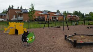 En park med gult slott att rutscha ner för, sandlåda, fjädergunga och nya radhus i bakgrunden.