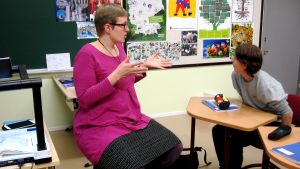 opettaja istuu sivustalla luokassa