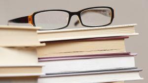 Glasögon på en hög med böcker.