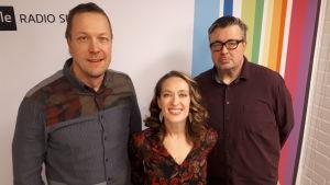 Mikko 'Peltsi' Peltola, Elsa Saisio ja Pekka Laine seisovat Radio Suomen tunnuksen edessä