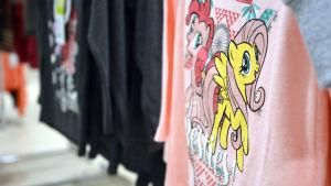 En rosa barntröja med flickiga, tecknade ponnytryck.