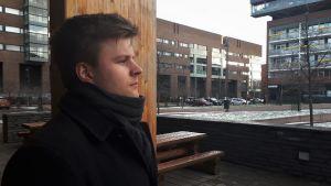 En man står framför en träpelare med höghus i bakgrunden.
