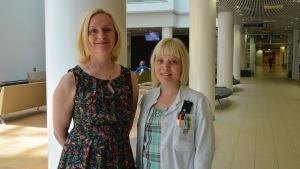 Outi Hirvonen och Mira Huhtala poserar i sjukhusets aula.