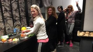 Joukko naisia laittamassa iltapalaa, yksi näyttää peace-merkkiä.