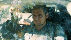 Mies istuu vakavana autossa, kuvattuna etulasin läpi, turvavyö kiinnitettynä.