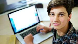 Kuvassa on tyytyväisen näköinen nuori poika tietokoneen äärellä.