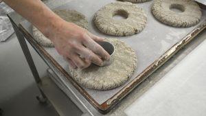 Händer trycker ut mitten av rågbrödet med en mettalform.