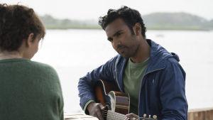 Jack (Himesh Patel) sjunger och spelar på gitarren vid en strand.