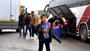 Pojke står framför två bussar