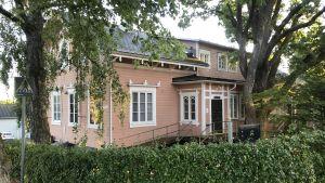 Bild på huset som har en brädfodring i gammalrosa och snickarglädje kring fönstren.