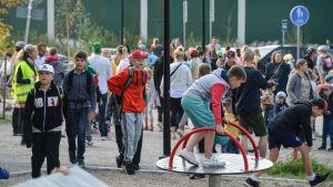 Massor med folk på skolgården, både barn och vuxna.