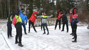 Elva vuxna i träningskläder står ute och värmer upp inför en långpromenad.