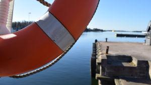 En orange livräddningsring hänger på en stolpe vid en förbindelsebåtsbrygga.