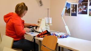 Jenni Saarinen syr med överlocksmaskin..