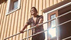 Musikern André Linman utomhus på en trappavsats, tittar upp mot solen.