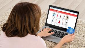 En kvinna ligger på en fluffig matta med en laptop framför sig och en nätbutikssida med dammode öppen på skärmen. Hon håller i ett kreditkort i handen och scrollar med den andra.