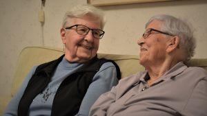 Två äldre kvinnor ser på varandra och ler.