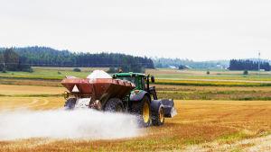 Traktor kör på åker. Samtidigt släpper den ner vitt pulver från släpet.