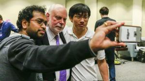 Kemipristagaren Sir Fraser Stoddart i en selfie med två studerande.