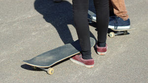 Fötterna på två ungdomar med skateboards.