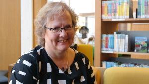 Lena Marander-Eklund  sitter framför en bokhylla.
