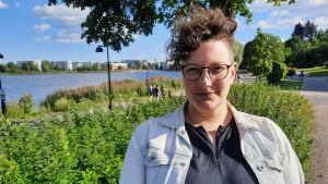 Pia Rickman i en ljus kavaj framför gröna buskar.