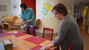 Två personer lägger ut bestick i matsalen i äldreboendet solglimten.