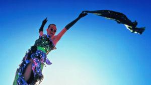 Hugo Weavingin näyttelemä drag queen hyppää ilmaan Australian erämaassa, täydessä loistossaan. Kuva elokuvasta Priscilla, aavikon kuningatar.