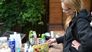 Kvinna står vid bord som fyllts av livsmedelsförpackningar.
