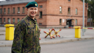 Stabchef Mika Immonen står vid porten till ett garnisonsområde. Han ler och tittar in i kameran.