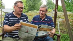 Två män sitter i en trädgårdsgunga och tittar i en papperstidning, Hangötidningen. Sommar, utomhus.